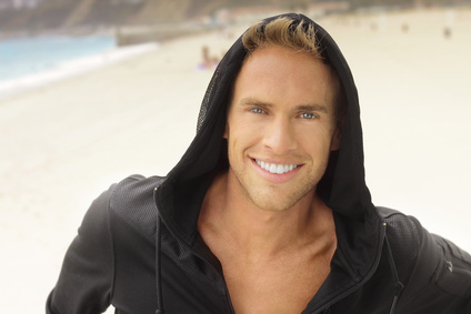 weiße Zähne -Young guy with great smile at the beach in active sportswear hood